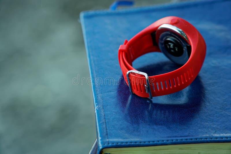 El reloj rojo del deporte en el cuaderno miente en la barandilla de madera en el parque, concepto del negocio imagen de archivo
