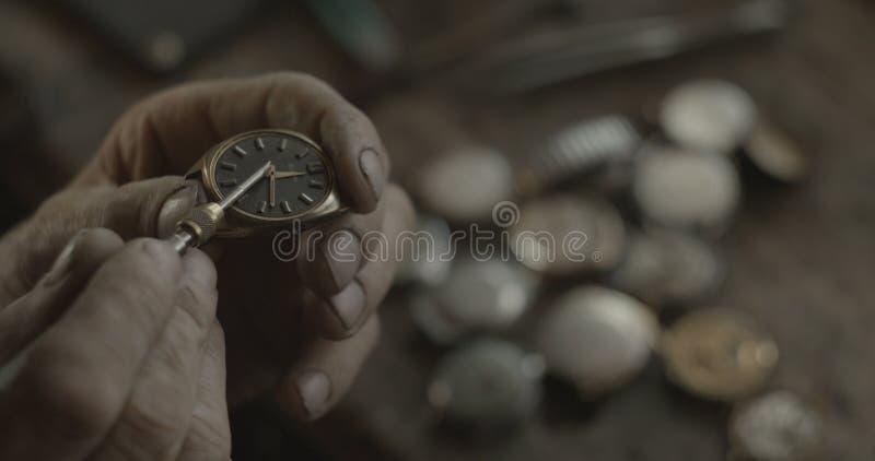 El relojero desconocido está fijando el reloj antiguo de la mano del vintage en su taller Ninguna cara 4K Tiro ROJO de la cámara imagenes de archivo