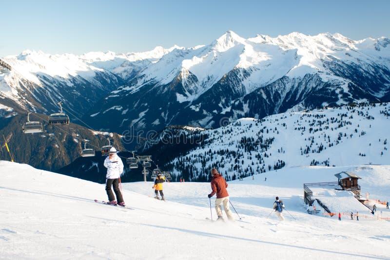 El remonte y el esquí se inclinan con los esquiadores debajo de él en día de invierno soleado con el cielo azul imagen de archivo