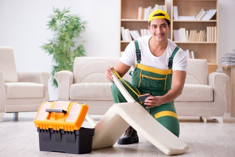 El reparador de los muebles que repara la butaca en casa foto de archivo