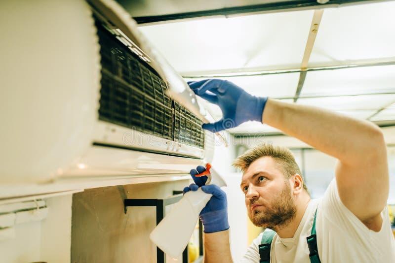 El reparador en uniforme limpia el aire acondicionado foto de archivo libre de regalías