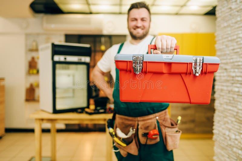 El reparador en uniforme sostiene la caja de herramientas, manitas foto de archivo libre de regalías