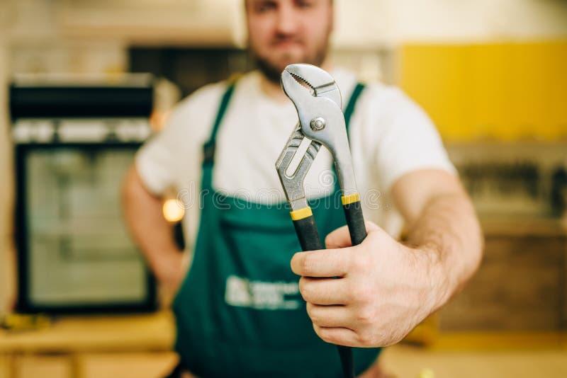 El reparador en uniforme sostiene la llave, manitas fotografía de archivo
