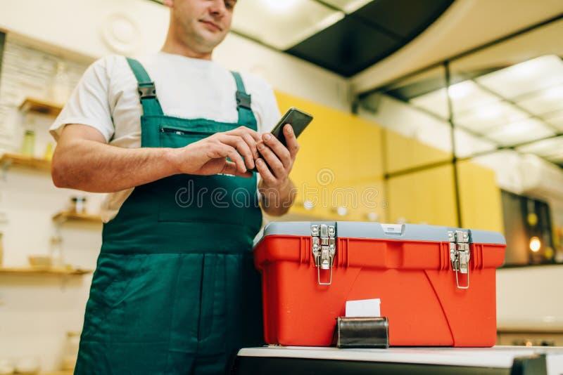 El reparador en uniforme sostiene el teléfono contra la caja de herramientas imágenes de archivo libres de regalías