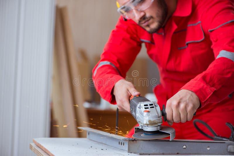 El reparador joven que trabaja con una muela abrasiva imágenes de archivo libres de regalías