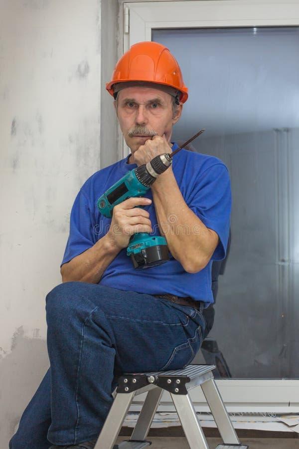 El reparador mayor se sentó en una escalera de mano y un pensamiento fotografía de archivo