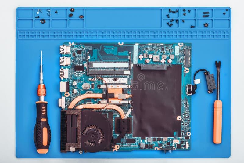 El reparador trabaja en soporte t?cnico, se engancha a la restauraci?n y a la limpieza del ordenador port?til foto de archivo