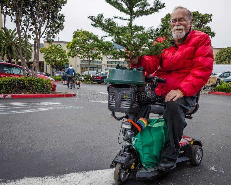 El residente mayor de Castro District está tomando a casa un árbol de navidad foto de archivo libre de regalías
