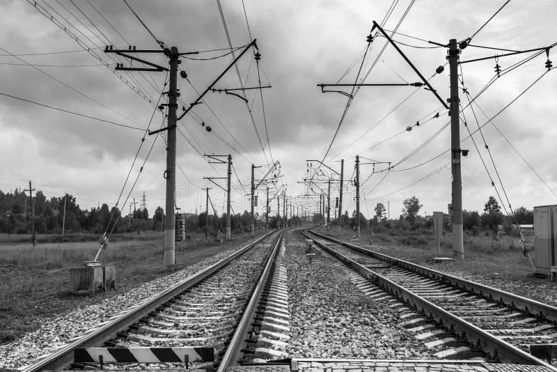 El retorcerse y el irse en las pistas ferroviarias de la distancia y los polos eléctricos a lo largo de ellos fotos de archivo libres de regalías