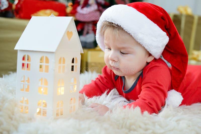 El retrato adorable del pequeño bebé lindo celebra la Navidad Días de fiesta del ` s del Año Nuevo Muchacho en un traje de santa  foto de archivo libre de regalías
