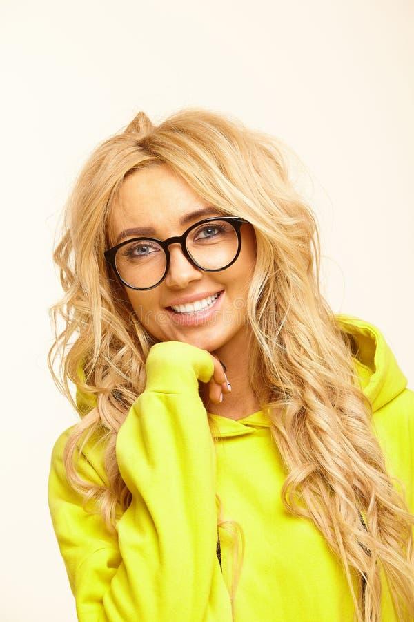 El retrato aislado de mujeres caucásicas felices con el pelo rubio, lleva alrededor de gafas y de sudadera con capucha amarilla fotografía de archivo libre de regalías