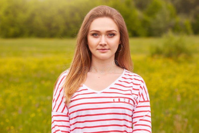 El retrato al aire libre de la muchacha sonriente feliz con el pelo recto largo en la camisa blanca con las rayas rojas que prese fotografía de archivo