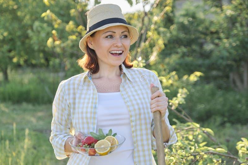 El retrato al aire libre de la mujer feliz 40 años, femenino en jardín en sombrero de paja con la placa de fresas acuña el limón imagen de archivo libre de regalías
