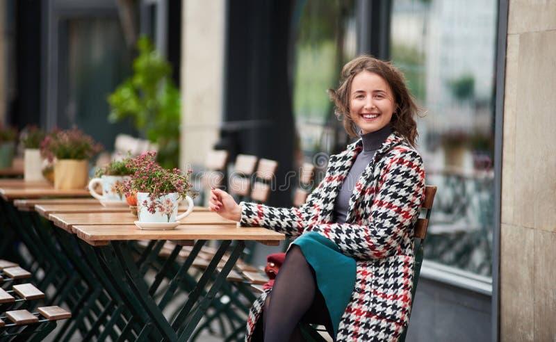 El retrato al aire libre de la mujer joven se está sentando en café de la calle foto de archivo libre de regalías