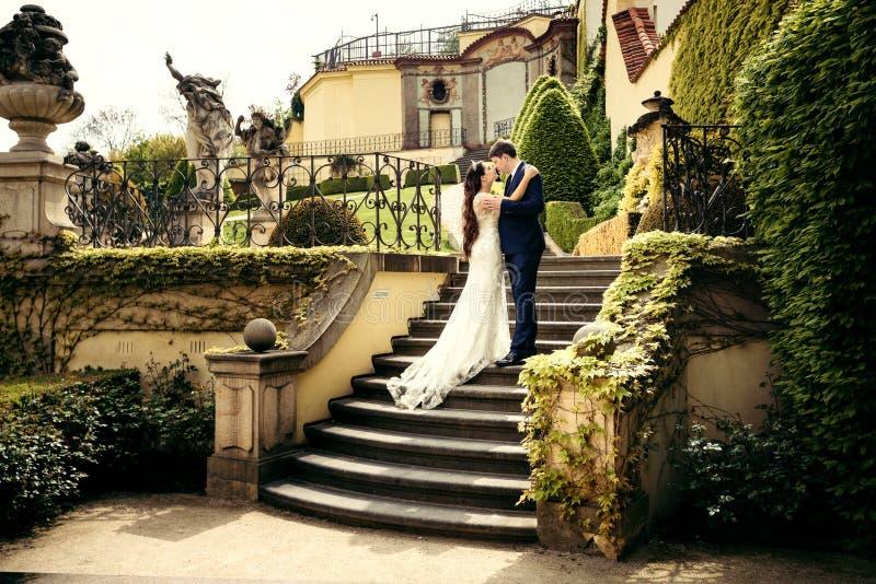 El retrato al aire libre horizontal de los recienes casados de abrazo felices que se colocan en las escaleras del castillo hermos foto de archivo libre de regalías