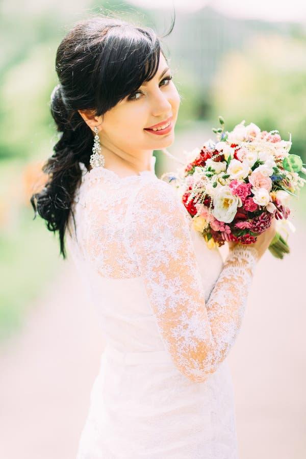El retrato al aire libre precioso de la novia sonriente que sostiene el ramo colorido de la boda imagen de archivo libre de regalías