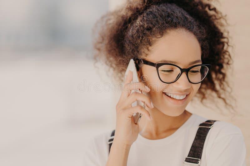 El retrato ascendente cercano de la mujer alegre con el pelo quebradizo, satisfecho con las tarifas para la llamada telefónica, e fotos de archivo