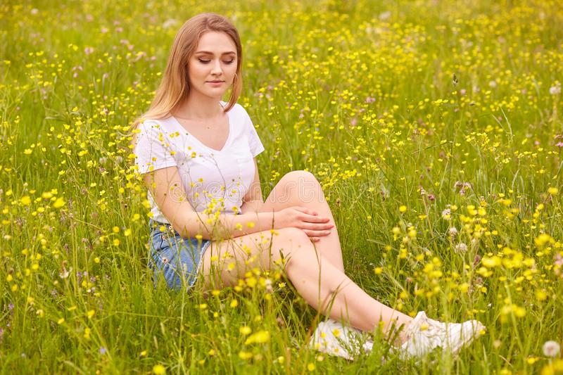 El retrato ascendente cercano de la mujer rubia modelo joven que se sienta en hierba, presentando en la camiseta del casul y la f foto de archivo