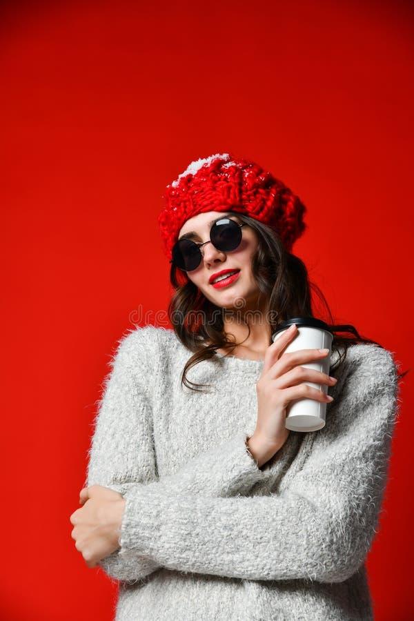 El retrato ascendente cercano de una chica joven sonriente en sostenerse del sombrero se lleva la taza de café fotos de archivo libres de regalías