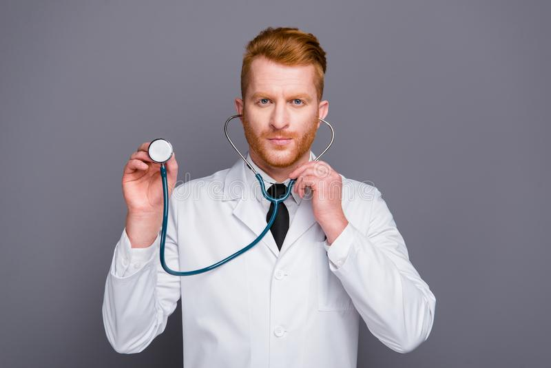 El retrato ascendente cercano del doctor atractivo sostiene el estetoscopio en oídos imagen de archivo libre de regalías