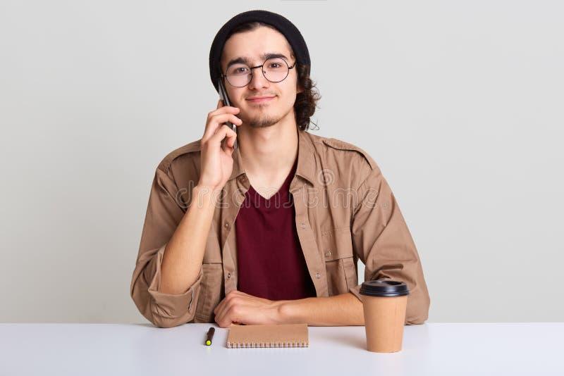El retrato ascendente cercano del hombre creativo ocupado llama al socio comercial para discutir la reunión futura, tiene nueva i fotos de archivo libres de regalías