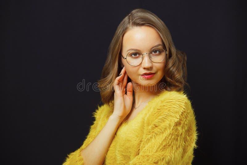 El retrato bastante femenino con el pelo marrón claro hermoso, lleva alrededor de las gafas, retrato del primer en negro aislado imágenes de archivo libres de regalías