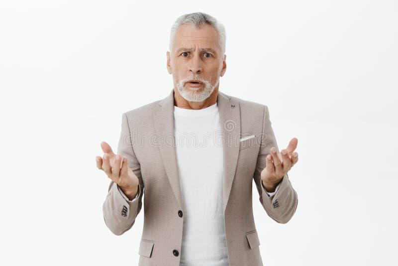 El retrato de confundido se preocupó al abuelo hermoso elegante en el traje formal que aumentaba las palmas cerca de pecho en ges fotos de archivo