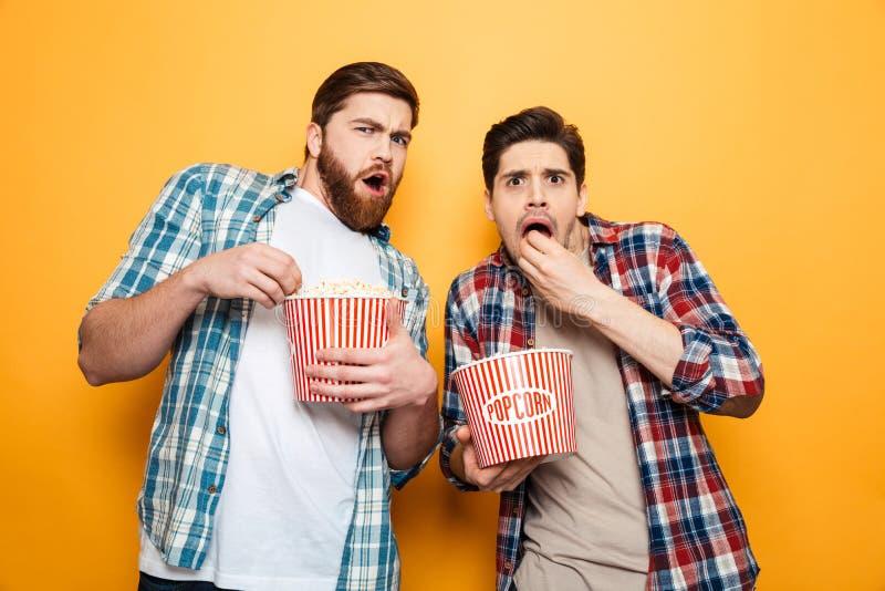 El retrato de dos asombró a los hombres jovenes que comían las palomitas imagen de archivo libre de regalías