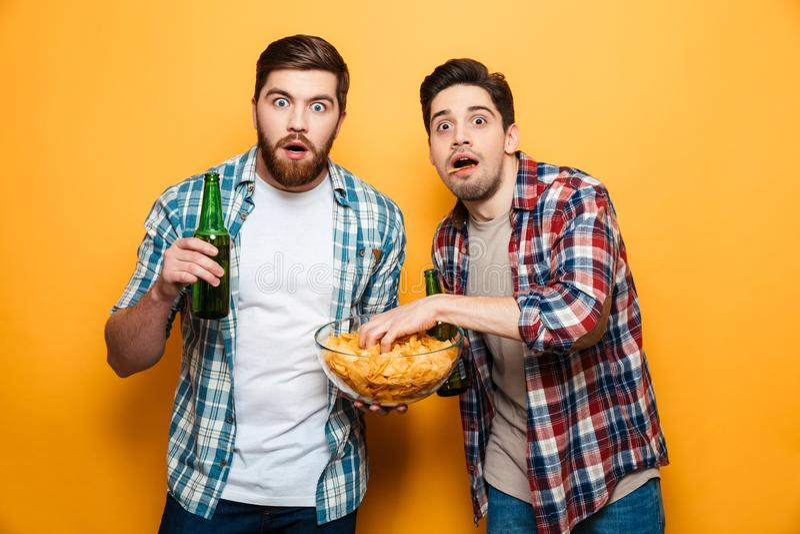 El retrato de dos asustó a los hombres jovenes que bebían la cerveza fotografía de archivo