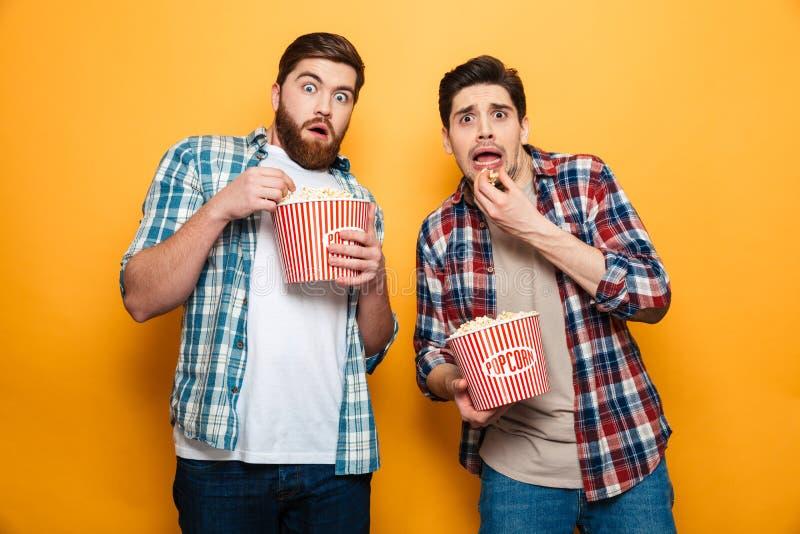 El retrato de dos asustó a los hombres jovenes que comían las palomitas imágenes de archivo libres de regalías