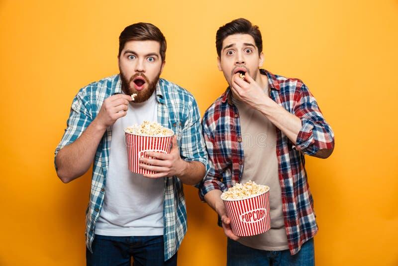 El retrato de dos asustó a los hombres jovenes que comían las palomitas imagen de archivo