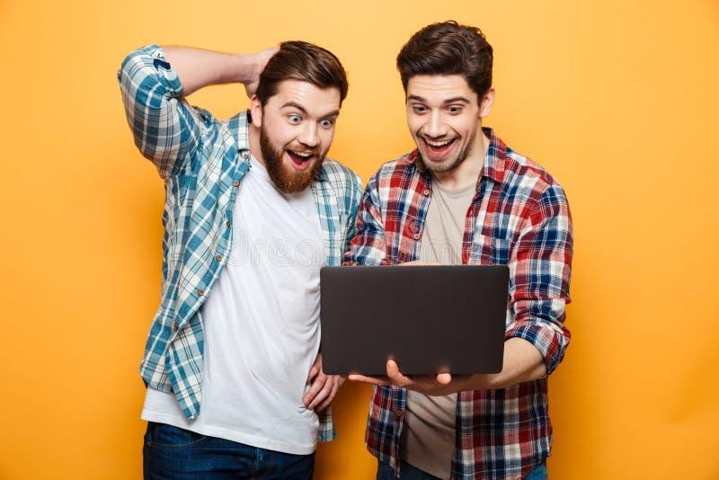 El retrato de dos excitó a los hombres jovenes que sostenían el ordenador portátil fotografía de archivo