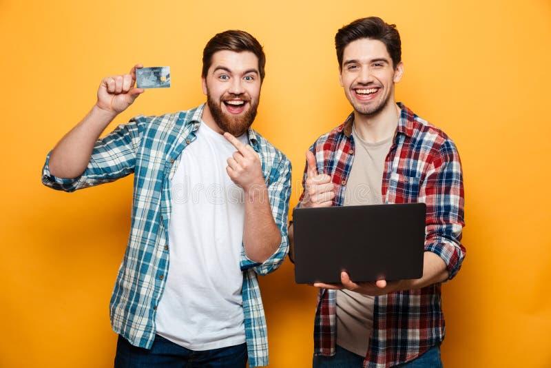 El retrato de dos excitó a los hombres jovenes que sostenían el ordenador portátil imagen de archivo