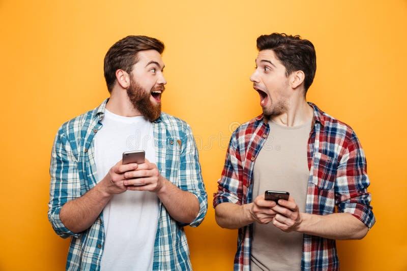 El retrato de dos excitó a los hombres jovenes que sostenían los teléfonos móviles fotos de archivo