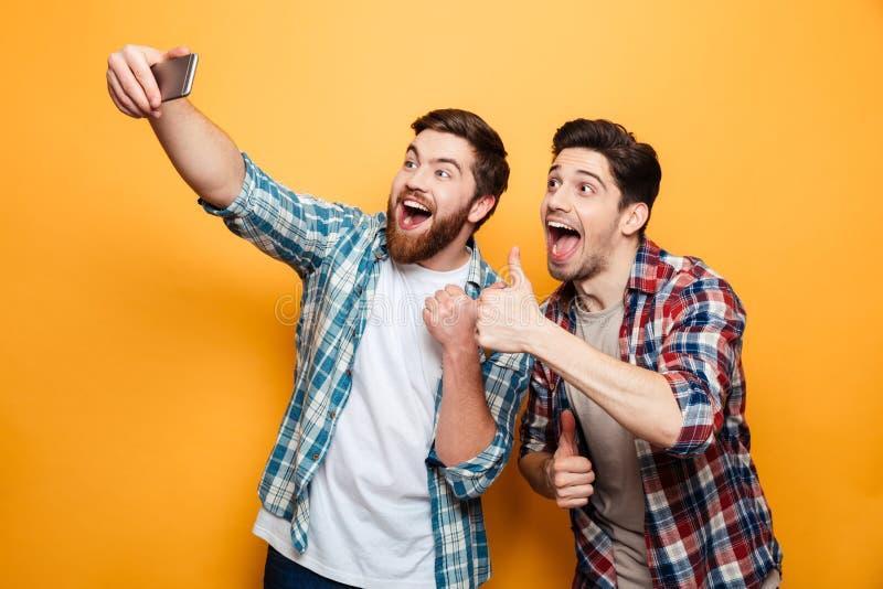 El retrato de dos excitó a los hombres jovenes que tomaban un selfie fotos de archivo