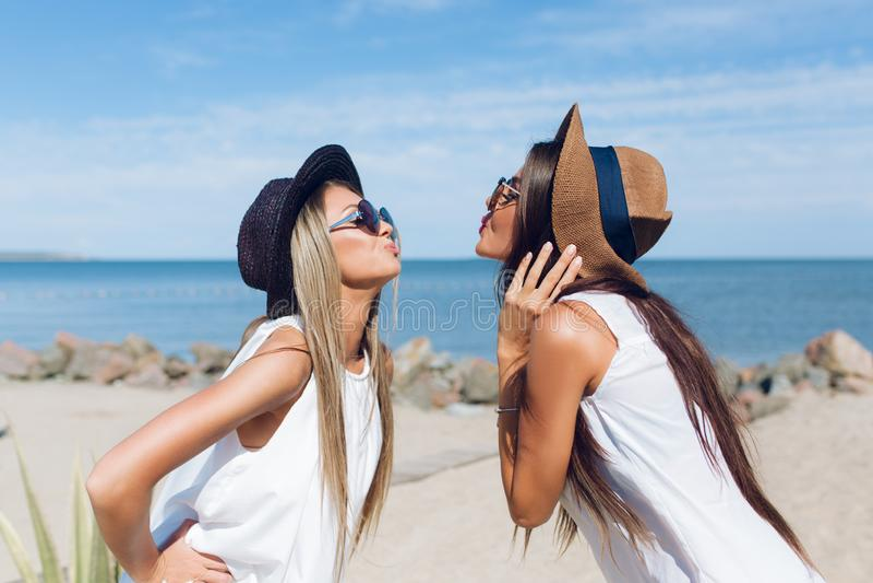 El retrato de dos muchachas morenas y rubias atractivas con el pelo largo se est? colocando en la playa cerca del mar Llevan los  imágenes de archivo libres de regalías