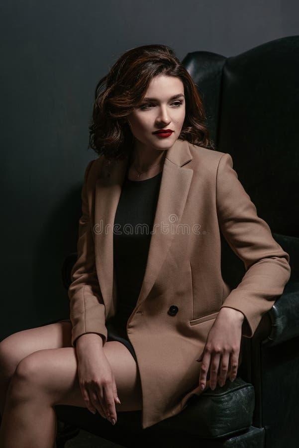 El retrato de jóvenes, mujer triste hermosa con el pelo marrón corto con elegante compone en vestido negro y chaqueta beige imagen de archivo libre de regalías