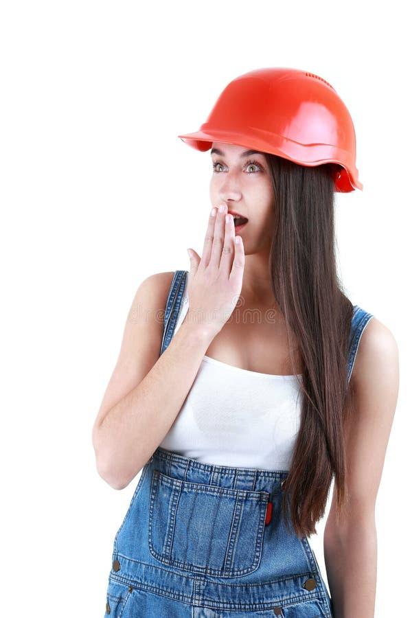 El retrato de jóvenes sorprendió al constructor de sexo femenino en guardapolvos y casco foto de archivo libre de regalías