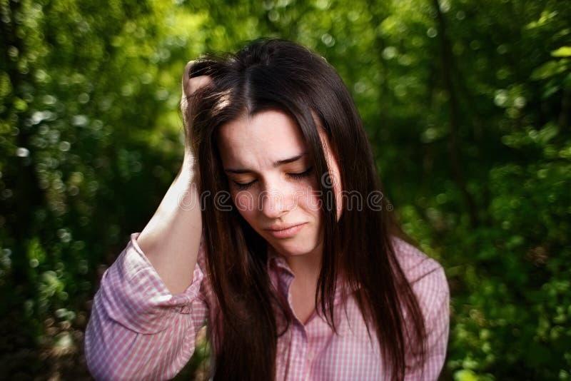 El retrato de jóvenes subrayó a la mujer que sufría de dolor de cabeza o de migr imágenes de archivo libres de regalías