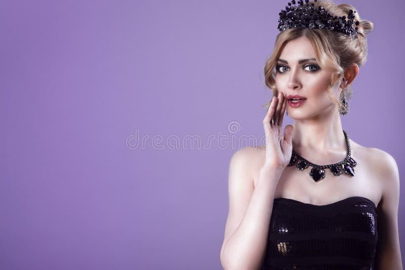 El retrato de la belleza del modelo rubio joven magnífico en top sin tirantes de la lentejuela con el pelo del updo y la joya neg imagen de archivo
