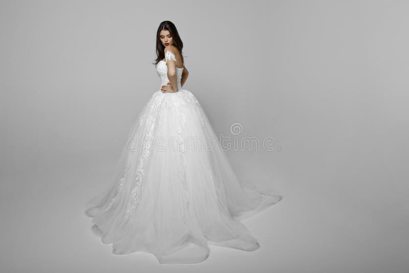 El retrato de la belleza de un modelo en vestido wendding, compone, colocando un lado, mirando abajo, isolaetd en el fondo blanco fotografía de archivo