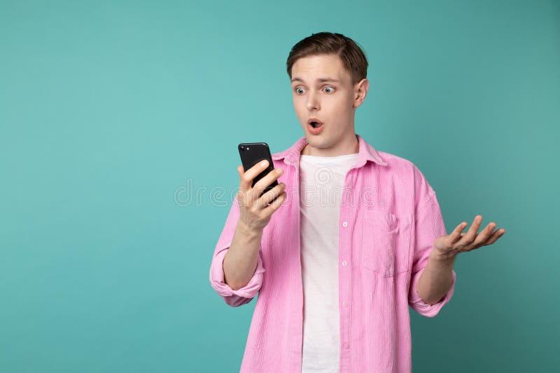 El retrato de la cara chocada y asustadiza del hombre europeo consigue gritado de smartphone fotografía de archivo libre de regalías