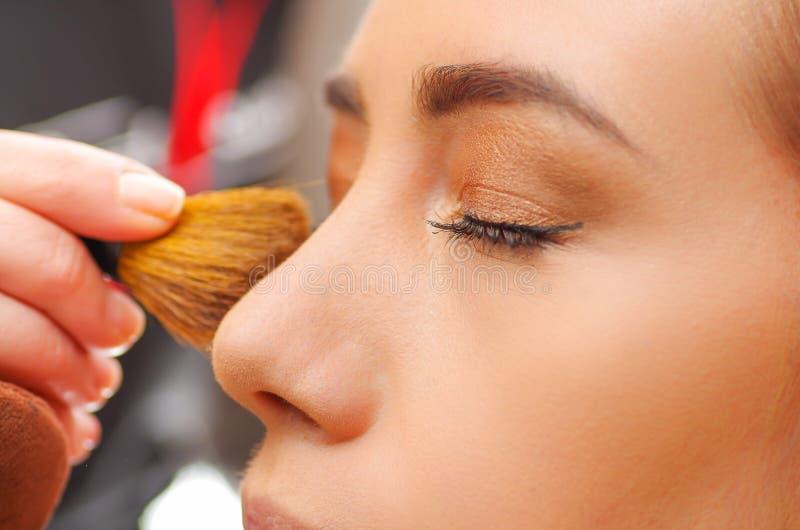 El retrato de la cara hermosa de la mujer joven que conseguía maquillaje, usando un cepillo, la señora cerró ojos con la relajaci imagen de archivo libre de regalías