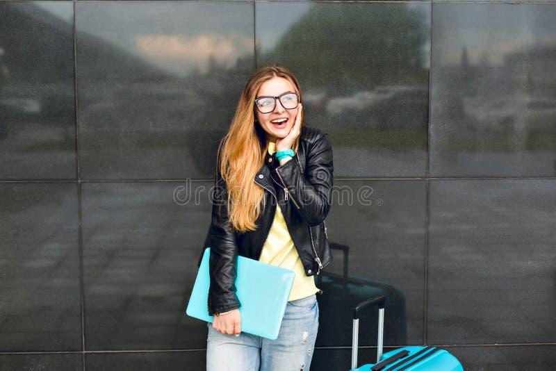 El retrato de la chica joven con el pelo largo en vidrios se está colocando afuera en fondo negro Ella lleva la chaqueta negra co foto de archivo