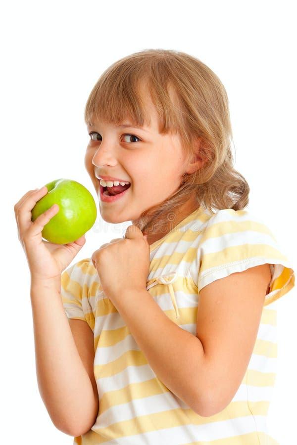 El retrato de la colegiala que comía la manzana verde aisló fotografía de archivo