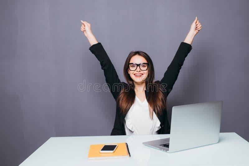El retrato de la empresaria acertada joven feliz celebra algo con los brazos para arriba La mujer feliz se sienta en la oficina y imagen de archivo
