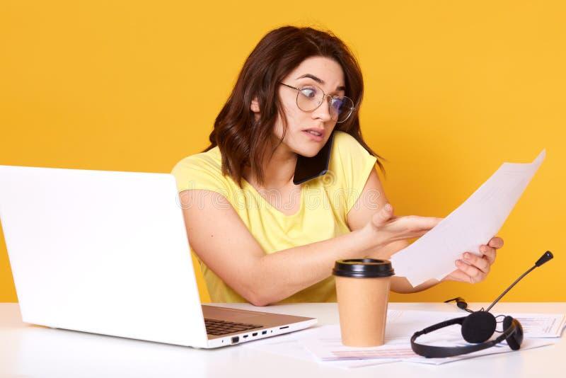 El retrato de la empresaria joven asombrosa que sostiene los papeles a disposición y que habla en el teléfono móvil, camiseta que imagen de archivo libre de regalías