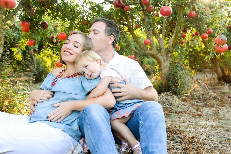 El retrato de la esposa husbent y embarazada feliz con la hija linda del bebé que se divierte resto y en la fruta del pomegrate c fotos de archivo