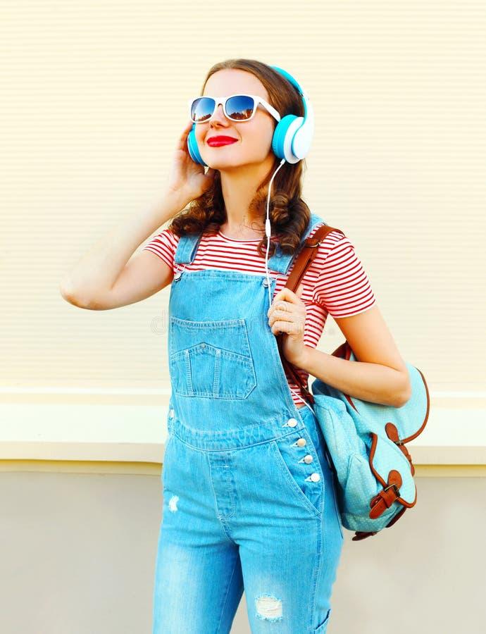 El retrato de la forma de vida de la moda que es la mujer feliz escucha la música en auriculares sobre blanco imágenes de archivo libres de regalías