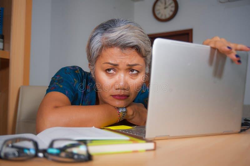 El retrato de la forma de vida de la oficina del centro triste y deprimido envejeci? a la mujer asi?tica atractiva que trabajaba  imagen de archivo libre de regalías